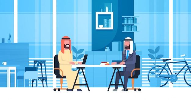 Homens de negócio árabes que sentam-se na mesa de escritório no espaço moderno de coworking que trabalha junto trabalhadores muçulmanos no centro dos colegas de trabalho
