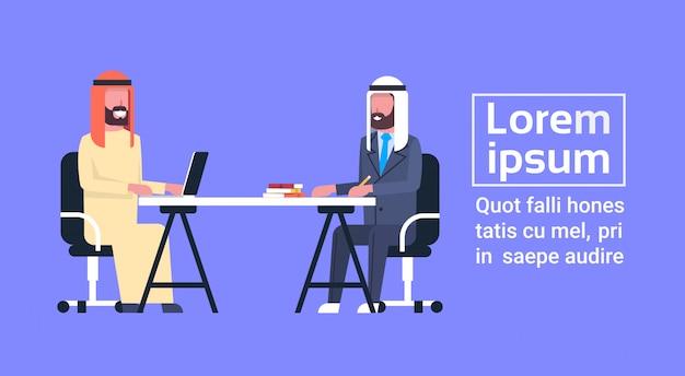 Homens de negócio árabes que sentam-se na mesa de escritório que trabalha junto reunião muçulmana dos trabalhadores ou entrevista