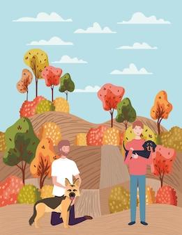 Homens jovens com mascotes de cães fofos no acampamento de outono