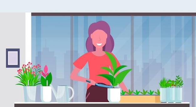 Housewife menina cute cultivar plantas mulher feliz cuidar da flor em potenciômetro moderno apartamento home jardinagem interior retrato horizontal