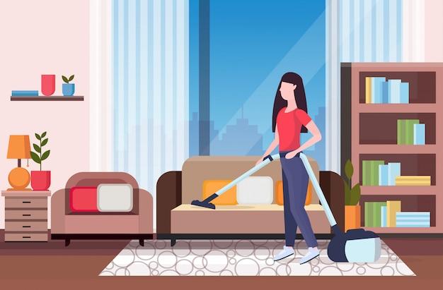 Housewife usando aspirador de pó menina fazendo o serviço doméstico serviço de limpeza serviço de limpeza conceito moderno sala de estar interior comprimento total apartamento horizontal