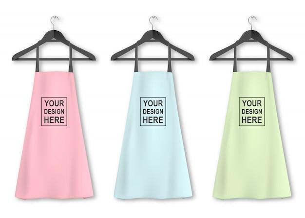 Ícone de avental de cozinha de algodão conjunto com cabides closeup no fundo branco. cores pastel. modelo, mock up para branding, publicidade etc. conceito de culinária ou padeiro