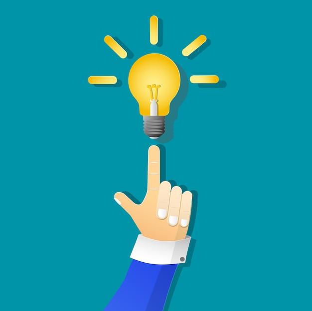 Ícone de lâmpada amarela e mão homem de negócios na arte de papel
