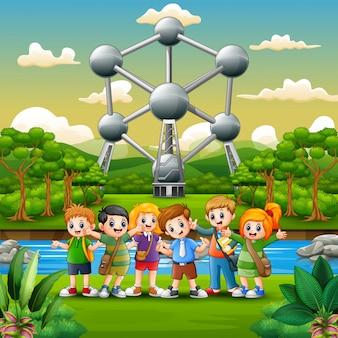 Ilustração de crianças em idade escolar feliz em pé na frente do atomium