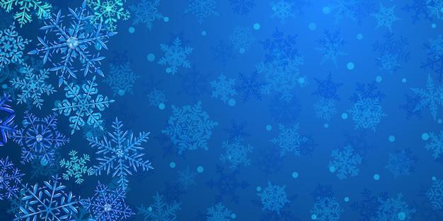 Ilustração de grandes flocos de neve de natal translúcidos complexos em cores azuis, localizados à esquerda, no fundo com neve caindo