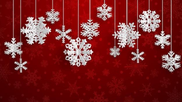 Ilustração de natal com flocos de neve de papel tridimensional branco pendurados sobre fundo vermelho