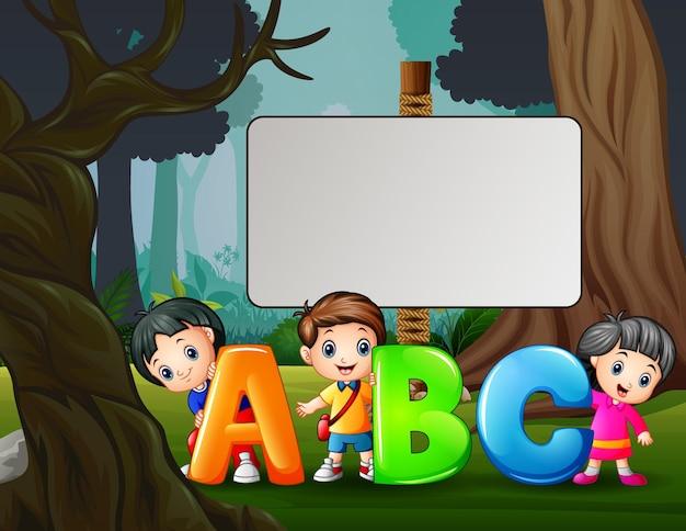 Ilustração dos desenhos animados de crianças felizes segurando a letra abc no parque