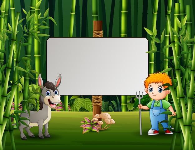 Ilustração dos desenhos animados de um jovem agricultor e um burro em pé perto da placa em branco