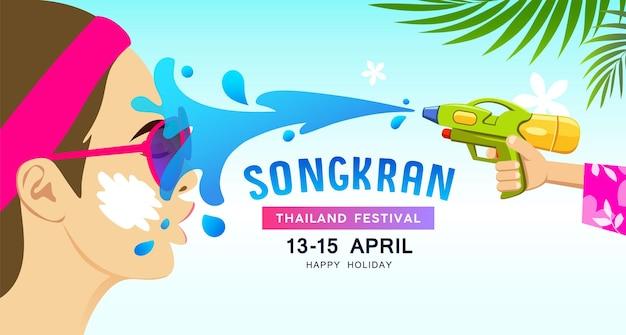 Incrível respingos de água do festival songkran tailândia na mulher do rosto com água de arma.