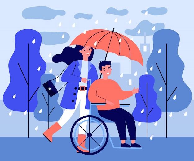 Indivíduo deficiente e assistente que andam na chuva
