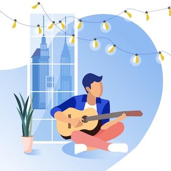 Indivíduo novo que senta-se no assoalho que joga a guitarra.