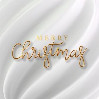 Inscrição dourada realista feliz natal em um fundo de seda branco. natal de texto metálico dourado para design de banner. molde de tecido de textura e folha.