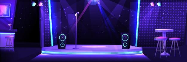 Interior da boate com um palco e um microfone para karaoke