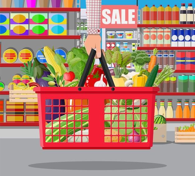 Interior da loja de supermercado com legumes na cesta de compras. grande centro comercial. loja interna dentro. balcão de checkout, mercearia, bebidas, alimentos, laticínios. ilustração vetorial em estilo simples