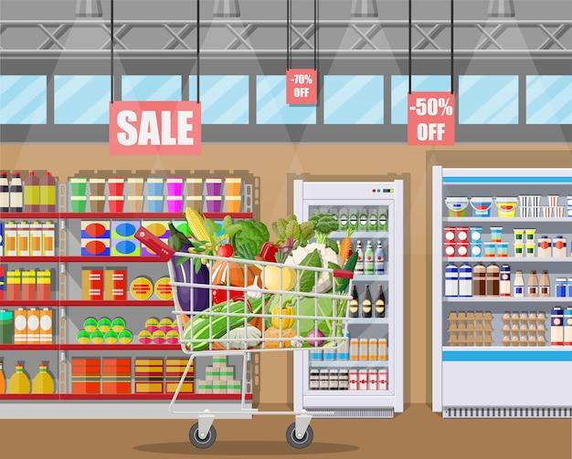 Interior da loja de supermercado com legumes no carrinho de compras. grande centro comercial. loja interna dentro. balcão de caixa, mercearia, bebidas, alimentos, laticínios