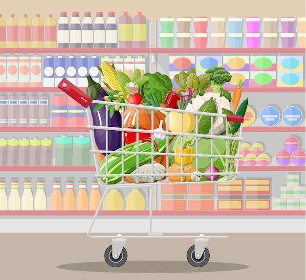 Interior da loja de supermercado com legumes no carrinho de compras.