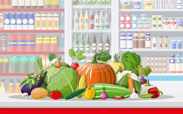 Interior da loja de supermercado com legumes.