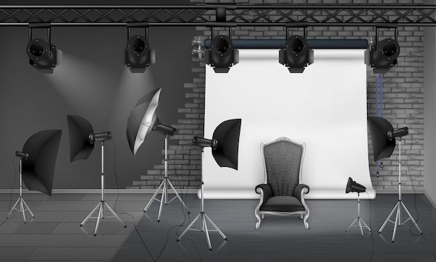 Interior de estúdio de fotografia com poltrona vazia, parede de tijolos cinza, tela de projeção branca, holofotes