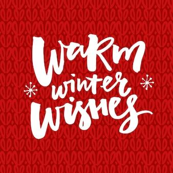 Inverno quente deseja texto sobre fundo vermelho de malha. cartão de natal com letras de escova.