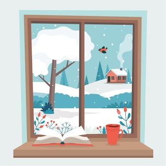 Janela de inverno com vista, um livro e uma xícara de café no peitoril.