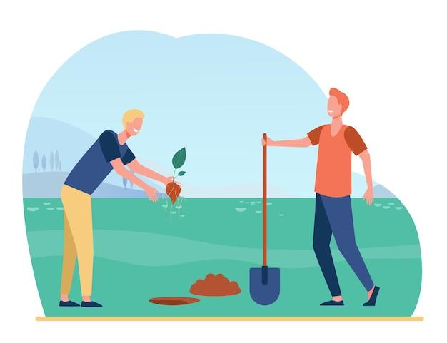 Jardineiros homens plantando brotos no solo