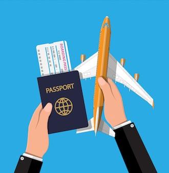 Jato de passageiros, cartão de embarque e passaporte na mão.
