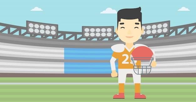 Jogador de rugby com bola e capacete nas mãos.