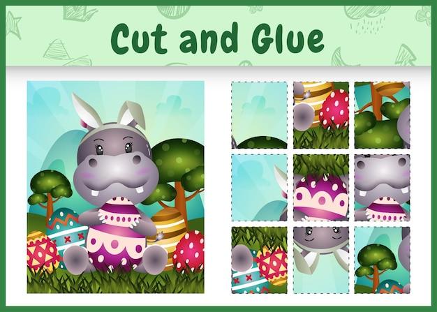 Jogo de tabuleiro infantil recortar e colar temático da páscoa com um hipopótamo fofo usando tiaras com orelhas de coelho abraçando ovos