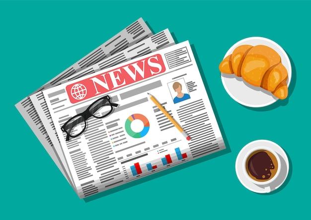 Jornal com croissant, xícara de café, lápis