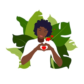Jovem africana abraça um grande coração com amor e carinho. conceito positivo de autocuidado e corpo. feminismo, luta por seus direitos, conceito de poder feminino. apartamento.