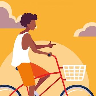 Jovem afro bicicleta com céu laranja