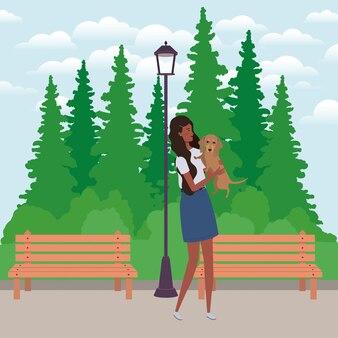 Jovem afro mulher levantando cachorro fofo no campo