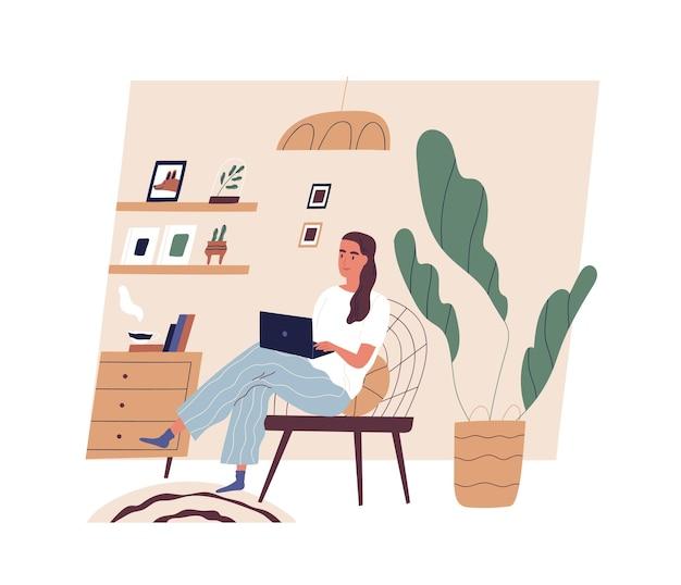 Jovem bonita sentada em uma cadeira confortável com um laptop em um quarto aconchegante
