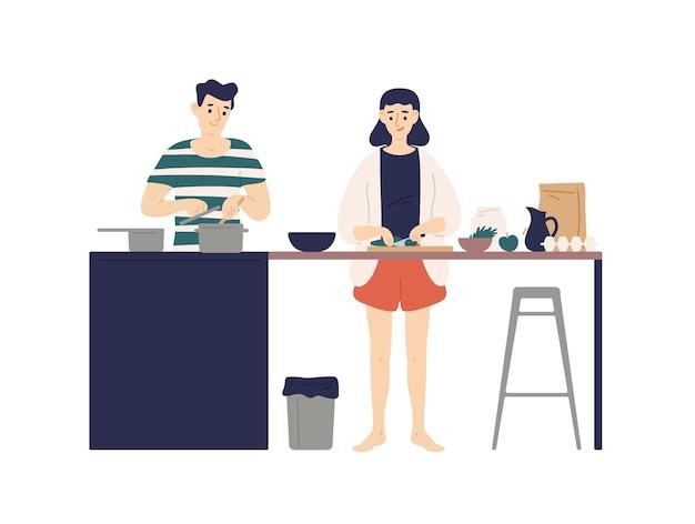 Jovem bonito e mulher cozinhando refeições na cozinha.