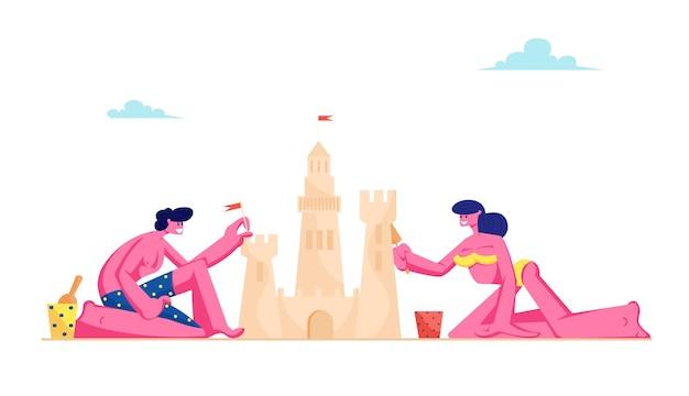 Jovem casal apaixonado se divertindo na praia de areia construindo um castelo de areia na ilha tropical à beira-mar
