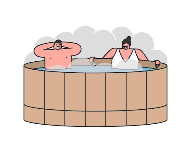 Jovem casal homem e mulher sentados na banheira de hidromassagem com vapor quente