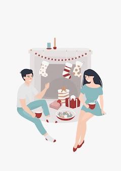 Jovem casal senta-se junto à lareira e bebe cacau rodeado de presentes de natal