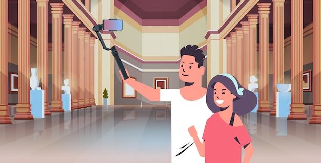 Jovem casal usando selfie vara tirando foto no smartphone câmera homem mulher visitantes na galeria de arte moderna museu salão interior retrato horizontal