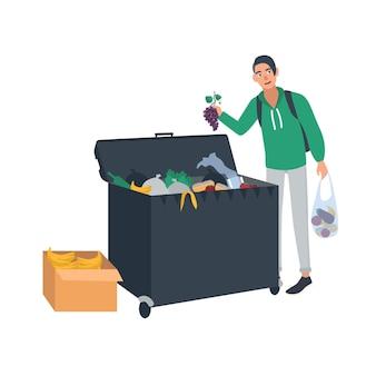 Jovem coleta frutas e vegetais do recipiente de lixo ou da lixeira.