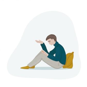 Jovem com cabelos castanhos em um suéter azul gasolina e calça cinza, sentado e lendo um livro. aluno a ler um livro.