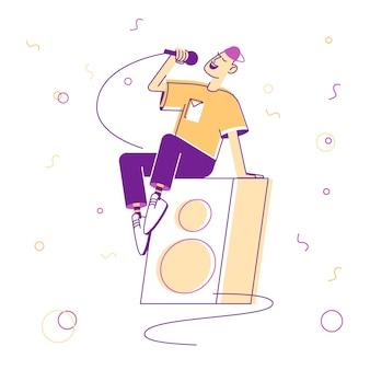 Jovem com roupas de adolescente sentado em uma enorme dinâmica no palco segurando o microfone