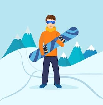 Jovem com roupas de inverno e óculos escuros, parado na encosta da montanha, segurando nas mãos uma prancha de snowboard
