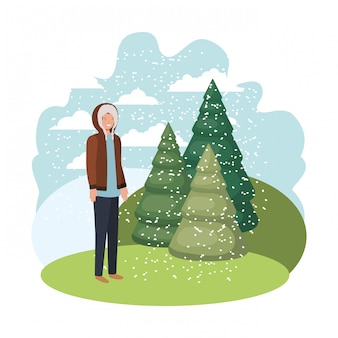 Jovem com roupas de inverno e pinheiros de inverno