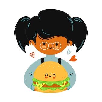 Jovem e fofa garotinha engraçada segurando o hambúrguer