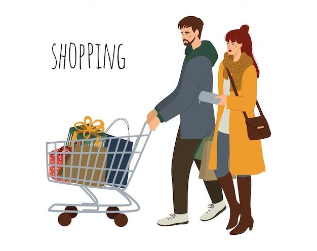 Jovem feliz casal com compras. homem com um carrinho de compras e uma mulher com os pacotes.