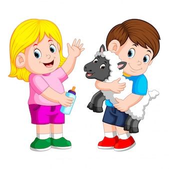 Jovem garota segurando a garrafa de leite de bebê e menino brinca com ovelhas