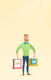 Jovem homem caucasiano feliz com sacolas de compras.
