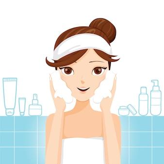 Jovem lavando o rosto com espuma no banheiro