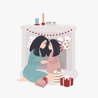 Jovem mãe e filha sentam-se junto à lareira e abrem os presentes de natal