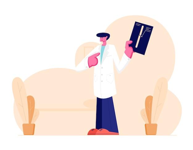 Jovem médico traumatologista em uniforme de manto branco apontando em imagem de raio-x com fratura de membro.